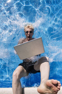 Shocked young man with laptop falling in swimming pool - JCMF01081
