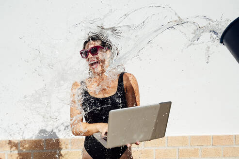 Water splashing on cheerful woman using laptop against wall - JCMF01084