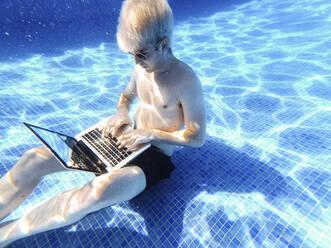 Shirtless young man wearing sunglasses using laptop underwater in swimming pool - JCMF01093