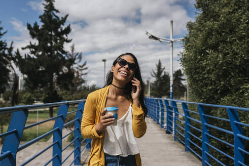 Cheerful woman wearing sunglasses talking over smart phone while standing on footbridge in park - DSIF00063