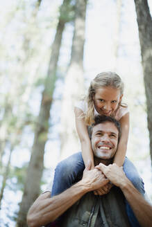 Smiling father carrying daughter on shoulders in woods - CAIF29135