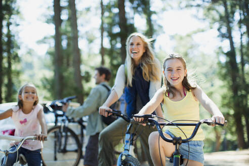 Smiling family bike riding in woods - CAIF29141