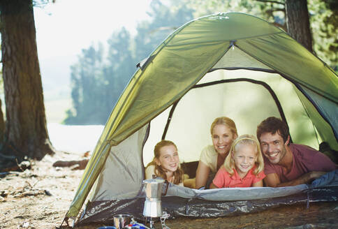 Smiling family inside of tent in woods - CAIF29147