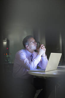 Pensive businessman working at laptop in office at night - CAIF29234