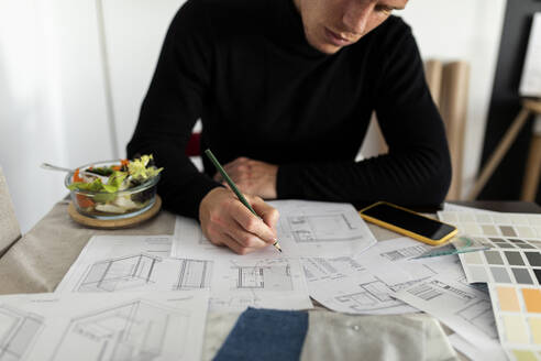 Male architect working on sketch at home office - VABF03177