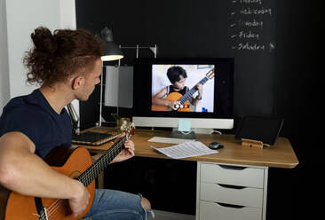 Man learning guitar while watching tutorial at home - VABF03183