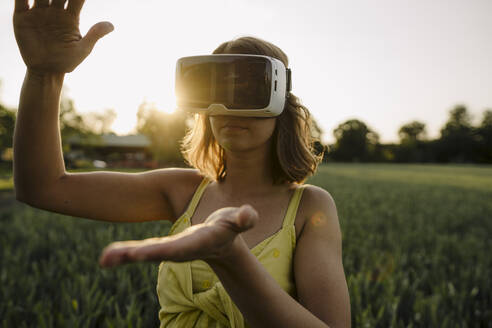 Young woman wearing VR goggles in a grain field in the countryside - GUSF04281