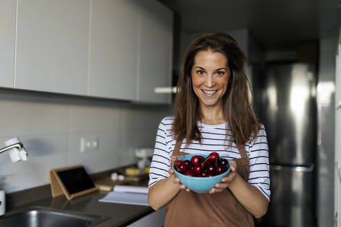 Smiling young woman holding cherries while standing in kitchen at home - VABF03240