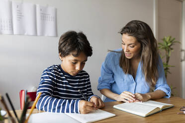 Female tutor assisting boy in writing homework on table at home - VABF03246