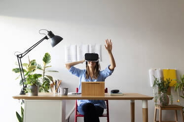 Young woman looking through virtual reality simulator while sitting at desk in home office - VABF03258