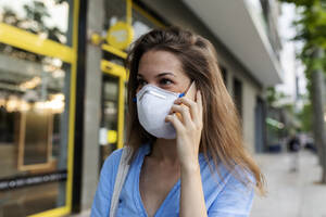 Close-up of young woman wearing mask talking over smart phone in city - VABF03261