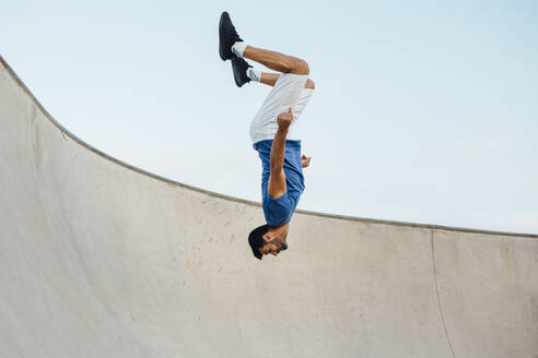 Upside down of young man doing wallflip on sports ramp against sky - MIMFF00098