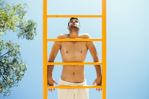 Shirtless man exercising on ladder against clear blue sky during sunny day - MIMFF00125