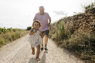 Grandfather running behind playful granddaughter on dirt road against sky - JRFF04650