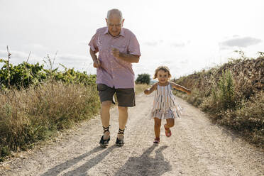 Playful senior man running with granddaughter on dirt road amidst plants - JRFF04653