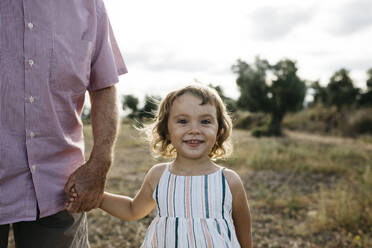 Smiling cute girl holding grandfather's hand while standing on land - JRFF04662