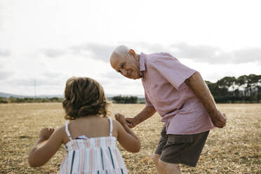 Grandfather looking at granddaughter while standing on land against sky - JRFF04668
