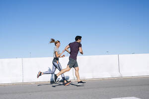 Couple running on road against clear blue sky in city during sunny day - JCMF01095