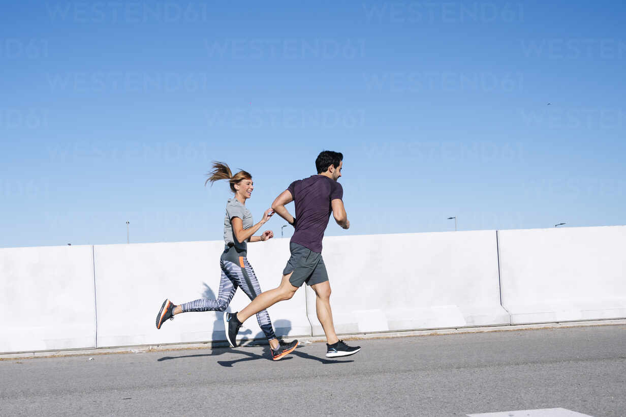 Couple running on road against clear blue sky in city during sunny day - JCMF01095 - Jose Luis CARRASCOSA/Westend61