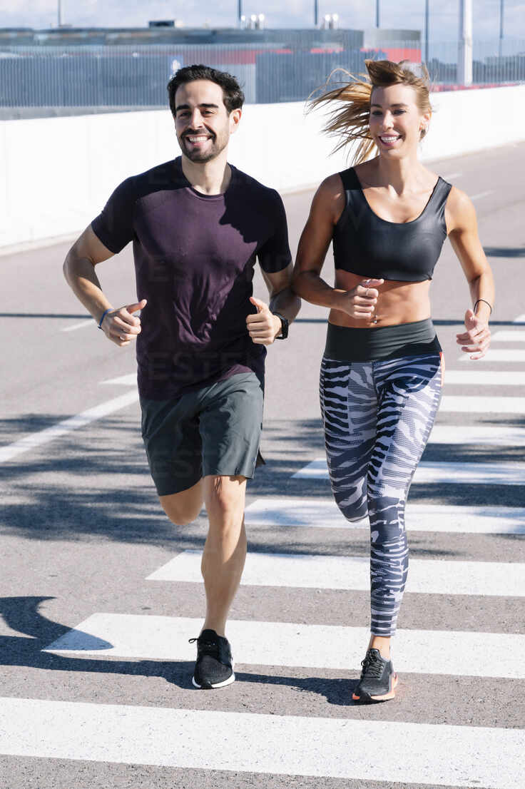 Smiling couple running on street in city during sunny day - JCMF01101 - Jose Luis CARRASCOSA/Westend61