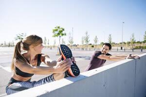 Smiling couple stretching on retaining wall against clear sky during sunny day - JCMF01104