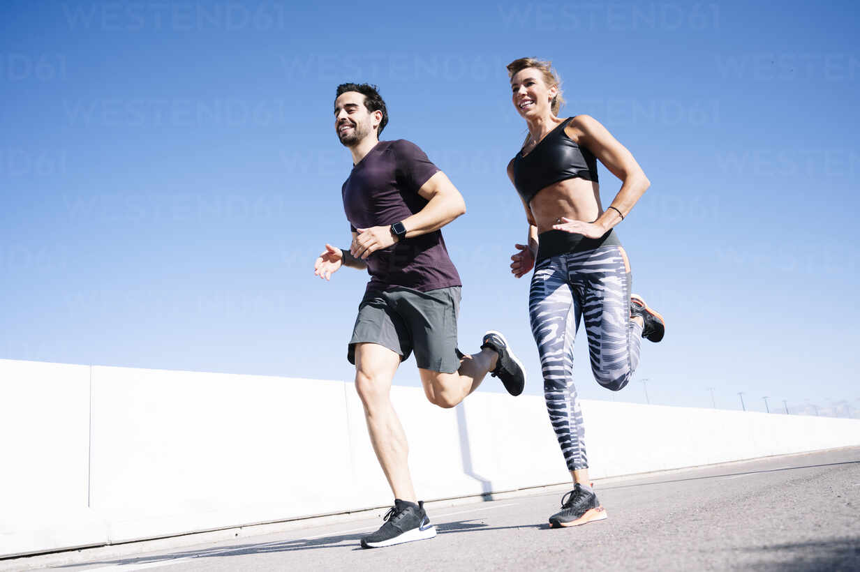 Smiling couple running on street against clear blue sky in city during summer - JCMF01107 - Jose Luis CARRASCOSA/Westend61