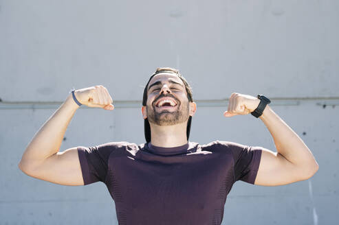 Happy man with eyes closed flexing muscles while standing against wall in city - JCMF01116
