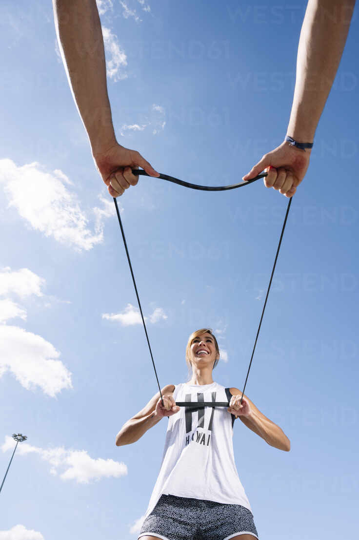 Couple exercising with strap against sky during sunny day - JCMF01134 - Jose Luis CARRASCOSA/Westend61