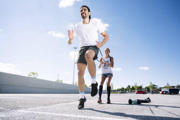 Couple exercising with strap while standing on road against sky during summer - JCMF01137