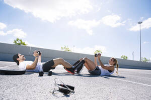 Couple holding dumbbells while lying on road against sky during sunny day - JCMF01140