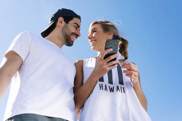 Smiling woman holding smart phone looking at boyfriend against clear blue sky - JCMF01143