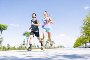 Mid adult couple running on road against blue sky during sunny day - JCMF01149