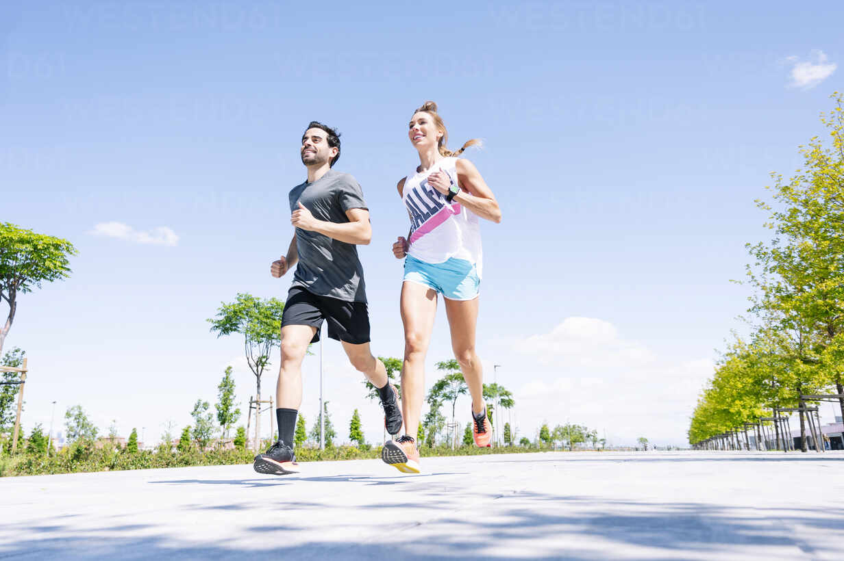 Mid adult couple running on road against blue sky during sunny day - JCMF01149 - Jose Luis CARRASCOSA/Westend61