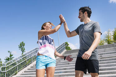 Cheerful couple giving high-five while standing on steps against blue sky in city - JCMF01152
