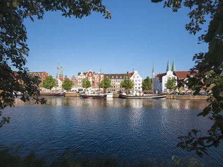 Germany, Schleswig-Holstein, Lubeck, Boats moored along bank of Trave with buildings of Travemunde in background - HAMF00692