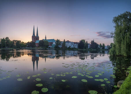 Germany, Schleswig-Holstein, Lubeck, Water lilies growing on bank of Trave at dusk with old town buildings in background - HAMF00695