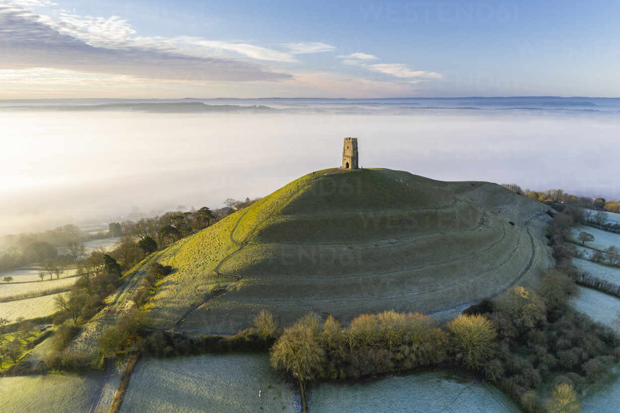 View by drone of St. Michael's Tower on Glastonbury Tor at dawn in winter,  Somerset, England,