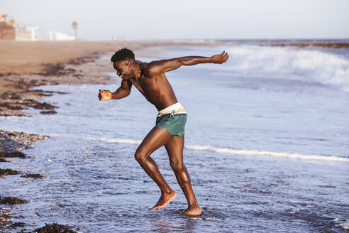Shirtless young man exercising at shore - LJF01703