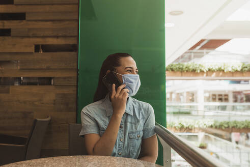 Young woman wearing mask talking over smart phone in mall - DSIF00064
