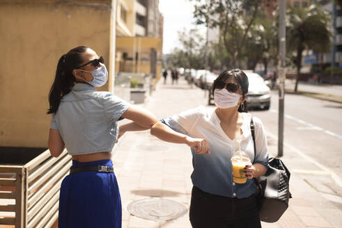 Female friends wearing sunglasses and masks giving elbow dump while standing in city - DSIF00067