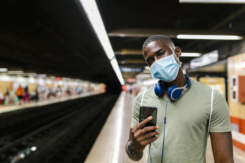 Young man wearing mask using smart phone while standing in subway station - EGAF00607