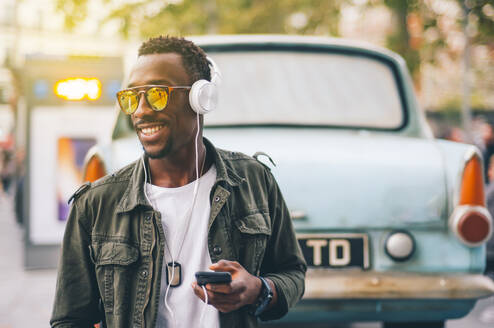 Smiling young man wearing sunglasses listening music through headphones against vintage car in city - OCMF01578