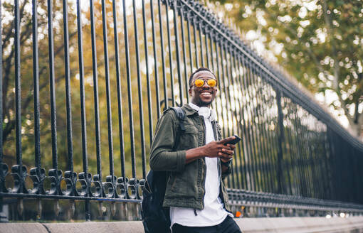 Smiling young man wearing sunglasses using mobile phone while standing against fence in city - OCMF01587