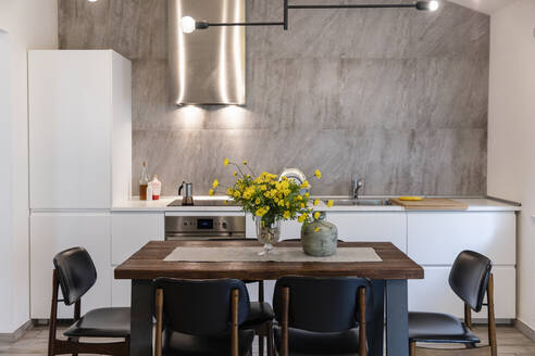 Dining table with chairs arranged in modern kitchen at home - EIF00140