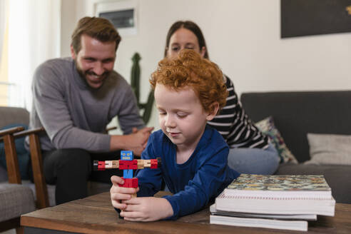 Parents looking at cute son playing with toy robot on table in living room - EIF00155