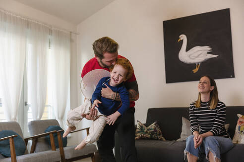 Happy woman looking at man carrying son with costume wings in living room - EIF00158