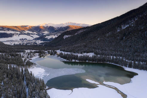 Sunrise over the village of Dobbiaco and frozen lake, Val Pusteria, Dolomites, Bolzano province, South Tyrol, Italy, Europe - RHPLF17055