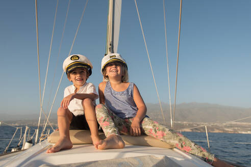 Positive kids in captain hats sitting on deck of expensive boat floating on water in sunny day - ADSF07318