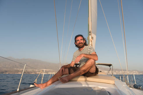 Positive bearded adult male in sunglasses sitting floating on expensive boat on sea in sunny day - ADSF07321