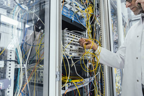 Mature man plugging in transceiver on fiber optic cable in data center - MFF05973